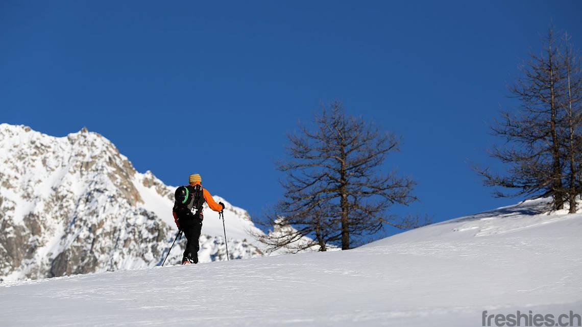 Tourengeher/Splitboarder beim Hochlaufen über offene Schneefläche